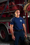 Stock picture of a strong brave young serious Latino fireman wearing a blue Tee shirt and standing in front of a fire Truck.